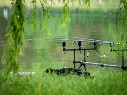 Fishing rod at the edge of a lake in Bucharest. Fishing on a beautiful day.