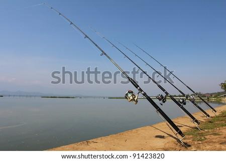 Fishing-rod at the lake under blue sky - stock photo