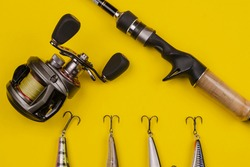 Fishing rod baitcasting reel and baits on a yellow background. Fishing, tackle, sport. Selective focus.