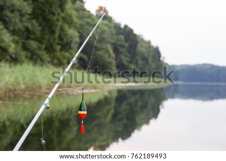 Fishing rod, fishing pole with a cork or float on the line and a colorful lake in background