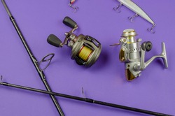 Fishing rod fly fishing reel, baitcasting reel and baits on blue background. Fishing, tackle, sport. Selective focus.