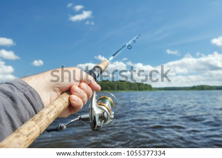 fishing rod in hand on the background of the shore, covered with green forest.Blue sky and water. #1055377334