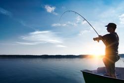 fishing rod lake fisherman men sport summer lure sunset water outdoor sunrise fish - stock image