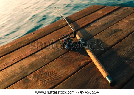 Fishing rod on a wooden dock. #749458654