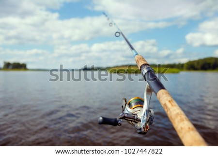 fishing rod on the background of a blurred islet of green grass. #1027447822