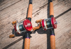 Fishing rod red and reel on wood table background , In the concept of fishing equipment