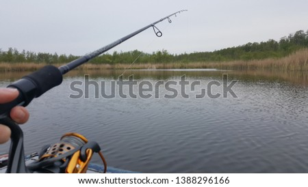 Fishing rod, spinning reel and oar boat on the lake or pier river bank. Sunrise. Misty fog against the backdrop of lake. The concept of rural getaway. Article about fishing day. #1388296166