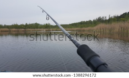 Fishing rod, spinning reel and oar boat on the lake or pier river bank. Sunrise. Misty fog against the backdrop of lake. The concept of rural getaway. Article about fishing day. #1388296172
