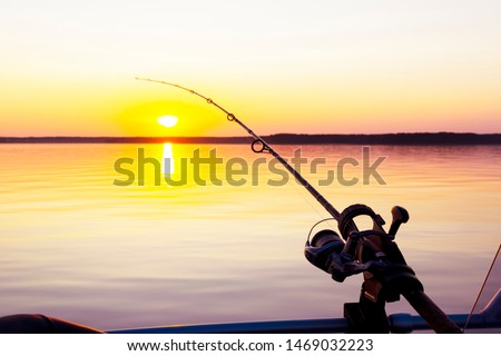 Fishing rod spinning with the line close-up. Fishing rod in rod holder in boat due the fishery day at the sunset. Rod rings. Fishing tackle. Fishing spinning reel.