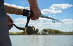 Fishing rod wheel close up in young man hands on the beautiful view of water and clouds