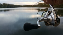 Fishing rod wheel closeup, beautiful lake and sunset