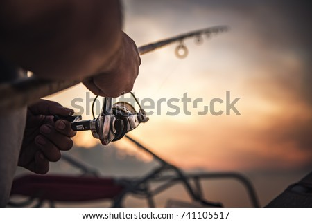 Fishing rod wheel closeup, man fishing with a beautiful sunrise behind him #741105517