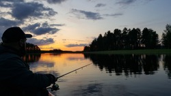 Fishing rod wheel closeup, man fishing with a beautiful sunrise/sunset behind him. Finland