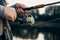 Fishing rod with a spinning reel in the hands of a fisherman. Fishing background.