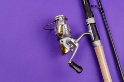 Fishing rod with attached fly fishing reel on blue background. Fishing, tackle, sport. Selective focus.