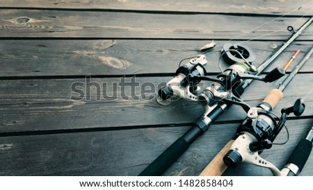 Fishing rods and reels on wooden background #1482858404
