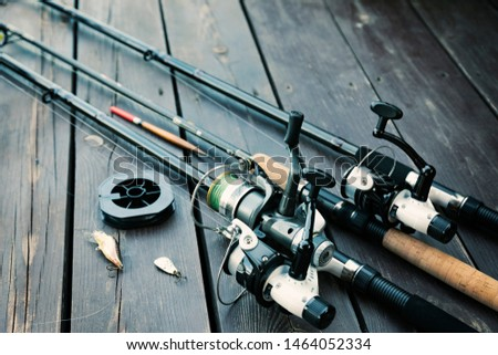 Fishing rods and reels on wooden background with text space #1464052334