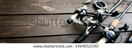 Fishing rods and reels on wooden background with text space #1464052340