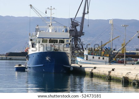 Fishing ship in port with little boat tied behind her - stock photo