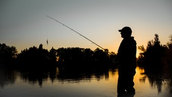 Fishing. spinning at sunset. Silhouette of a fisherman