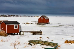 Fishing stage shacks and old wooden skiff row boat at shore of frozen North Atlantic Ocean in outport town of Joe Batt's Arm on Fogo Island, Newfoundland, NL, Canada