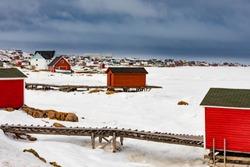 Fishing stage shacks of outport fishing village of Joe Batt's Arm at shore of frozen North Atlantic Ocean on Fogo Island, Newfoundland, NL, Canada