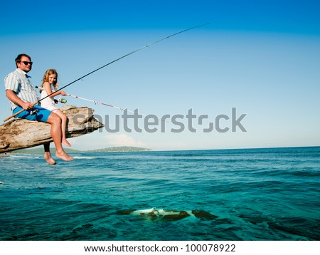 Fishing, summer beach - little girl fishing with father at the beach (space for text)