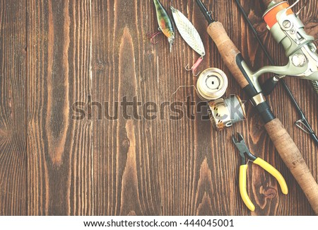 Fishing tackle - fishing spinning, fishing line, hooks and lures on wooden background. Toned image #444045001