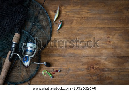 Fishing tackle - fishing spinning, hooks and lures on darken wooden background.Top view. #1032682648