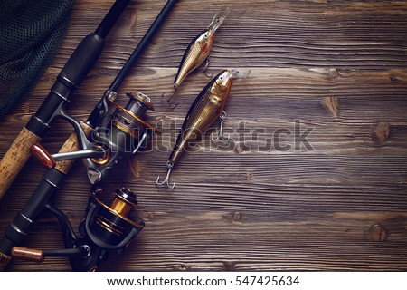 Fishing tackle - fishing spinning, hooks and lures on darken wooden background.Top view. #547425634