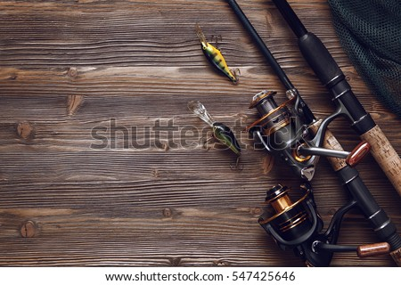 Fishing tackle - fishing spinning, hooks and lures on darken wooden background.Top view. #547425646