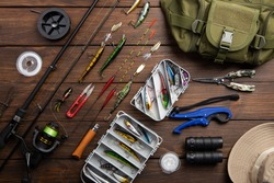 Fishing tackle - fishing spinning rod, hooks and lures on vintage wooden background. Active hobby recreation concept. Top view, flat lay.