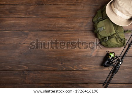 Fishing tackle - fishing spinning rod, hooks and lures on vintage wooden background. Active hobby recreation concept. Top view, flat lay. Copy space for text