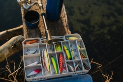Fishing tackle - fishing spinning, rod, reel, hooks, fly, bait, lures in box on wooden pier on pond background. Fishing day. Top view. Fishing for pike, perch. Recreation. Vintage banner. Closeup.