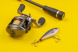 Fishing tackle for predatory fish. Fishing rod with reel and bait on yellow background. Casting rod with a multiplier reel and fishing line. Artificial bait. Selective focus.