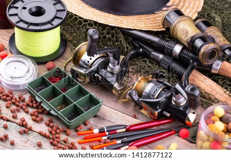 fishing tackle on a wooden table.  #1412877122