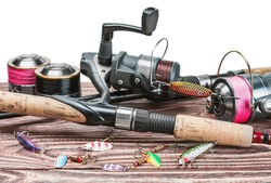 fishing tackle on a wooden table isolated on a white background. Focus on spinning.