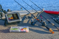 Fishing tackle set and fishfinder, echolot, sonar at the boat. Spinning rods with reels and lures