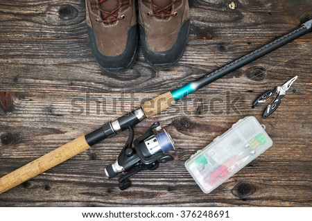 fishing tackles and fishing gear on wooden background, top view