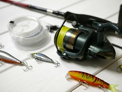 Fishing tackles lay on white wooden boards. Set of fishing tackles. Close up view on spool, rod, wobblers and lines.