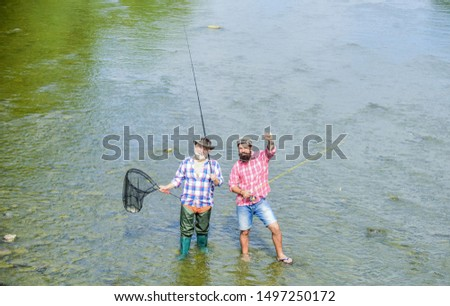 Fishing team. Happy fisherman with fishing rod and net. Hobby and sport activity. Male friendship. Father and son fishing. Summer weekend. Fishing together. Men stand in water. Nice catch concept. #1497250172