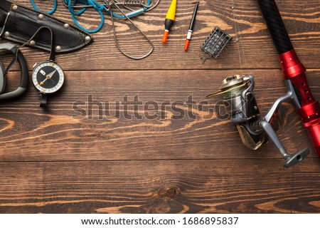 Fishing theme. Frame with reel, rod, fishing buoy, compass, feeder, knife and fish string on wooden background. Free space Zdjęcia stock ©