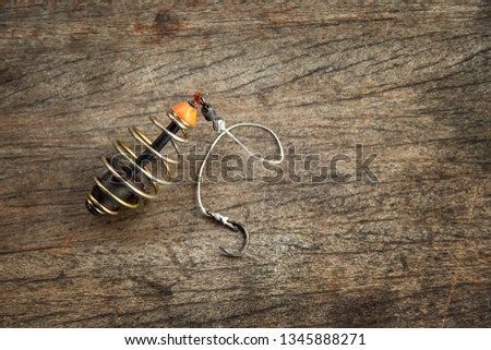 Fishing tools Spring feeder with lead sinker and next is hook on wood background. #1345888271