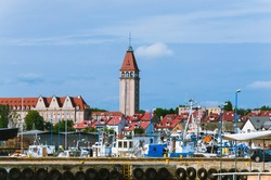 Fishing town of Władysławowo in Poland. A tourist town on the Baltic Sea. View of the tall lighthouse and boats moored in the harbour.