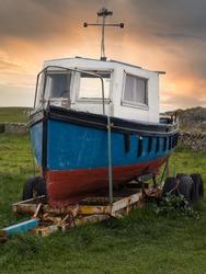 Fishing trawler on trailer at sunset