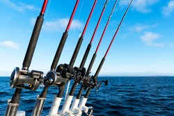 Fishing trolling boat rods in rod holder. Big game fishing. Fishing reels and rods pattern on boat. Sea fishing rods and reels in a row