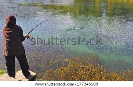 Fishing veiled woman at lake garden  #177346508