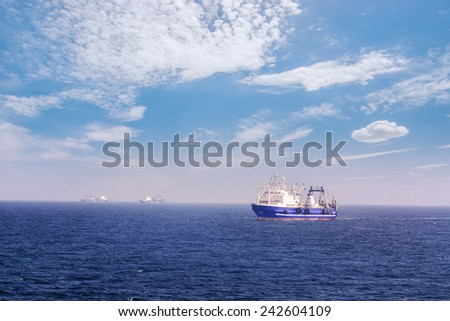 Fishing vessel for fishing in the sea. A Sunny day. Calm weather. Several ships.