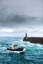 Fishing vessel under storm arriving at pier.  It's a boat or ship used to catch fish in the sea. Fishing can be affected by storms. Storms implies conditions like strong wind, precipitations or rain.