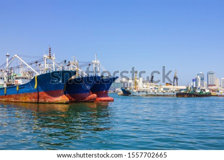 Fishing vessels, cargo ships in the port on the roadstead. On the shore of the city, tall buildings. Bright sunny day. #1557702665